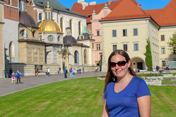Curious Claire standing in front of the colourful Wawel Royal Castle in Krakow