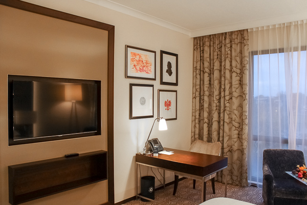 A spacious room with a desk in the corner and a large LCD TV on the wall