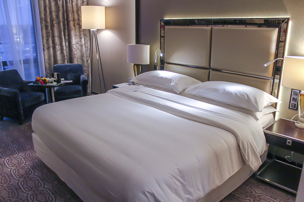 A spacious looking room with a pristine looking bed. The sheets are clean and white and very inviting