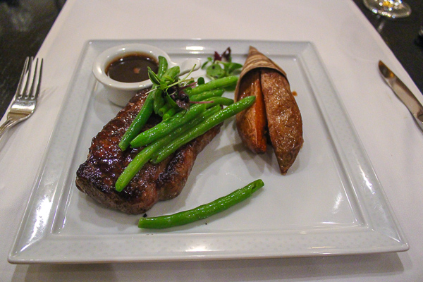 A melt in your mouth looking steak with bright vibrant green beans on top and carefully cut chips