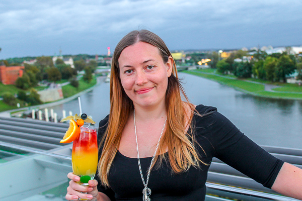 Curious Claire holding a colourful cocktail with the Wawel River in the background - She is smiling because this is a great hotel in Krakow