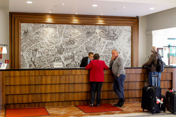 The pristine reception area at Sheraton Grand Krakow where a polite staff member is helping out guests
