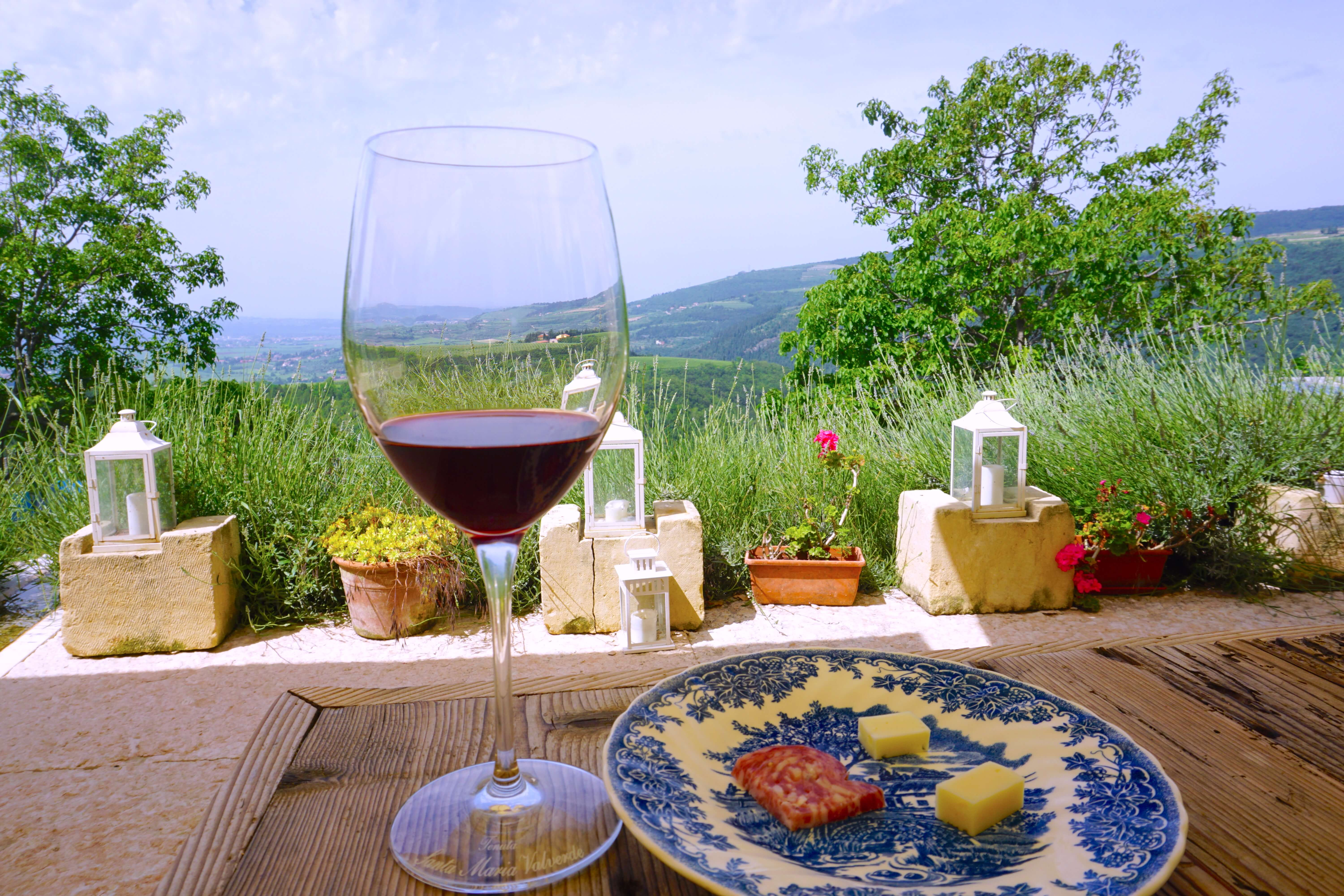 A glass of red Valpolicella wine and a plate of delicious local Italian salami and cheese