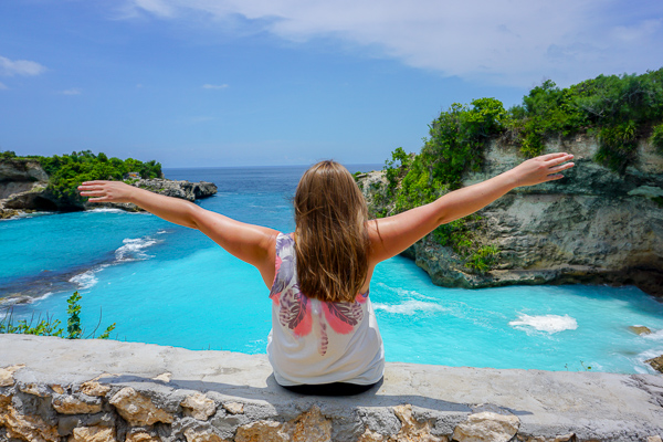 Loving life, sitting on a wall overlooking a beautifully clear blue ocean in Indonesia