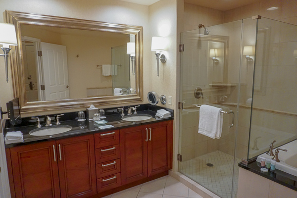 The spacious bathroom with walk in shower and marble work top with 2 sinks