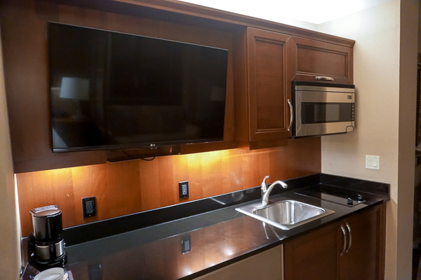 The spacious kitchenette with a coffee maker, kettle, microwave, fridge, sink and 2 stove top