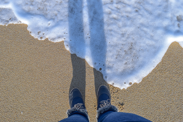 Wearing fluffy winter boots on a gorgeous sandy beach