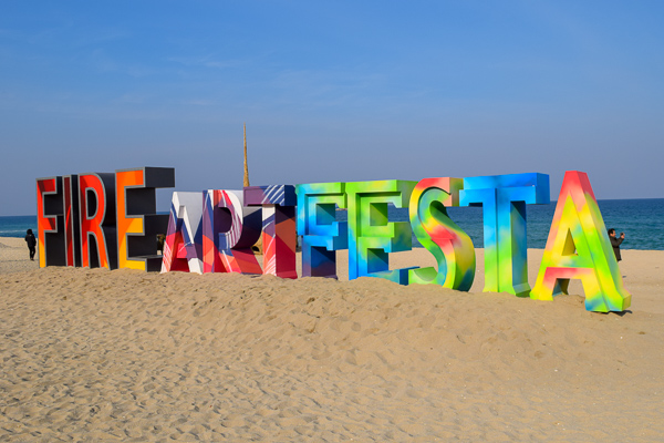 Colourful statue with the words 'Fire Art Festa' located on a beautiful sandy Korean beach
