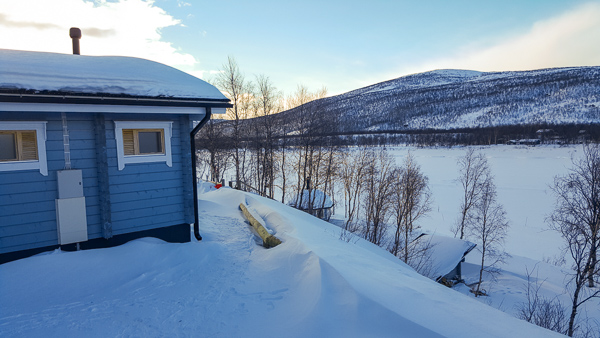The cute blue cottage of Aurora Holidays overlooking the frozen river with Norway in the background