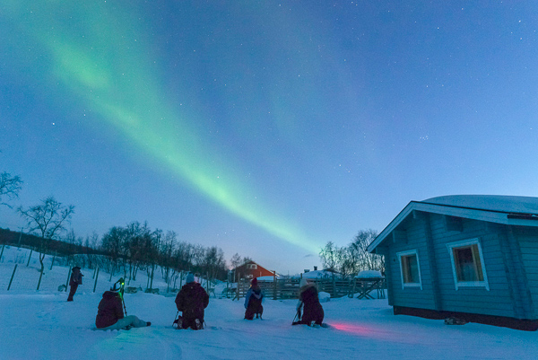 Aurora Holidays cottage in the evening - 4 people are on the floor with cameras and tripods taking shots of the northern lights in the sky