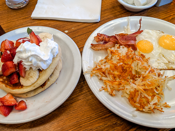Two plates on a table. The first is a pile of fluffy pancakes topped with whipped cream and strawberries. The second plate has crispy bacon, fried eggs and crispy hash browns. This is why Denny's is a great breakfast spot in Las Vegas