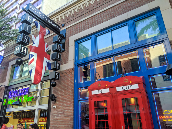 A 'Fish & Chips' sign with a dangling fish painted in the British Union Jack outside of a restaurant with red telephone boxes as doors - a great restaurant in Las Vegas