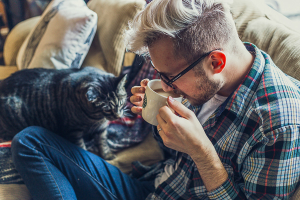 A man drinking coffee and letting the cat interact with him - the best way to act when visiting a cat cafe in the UK