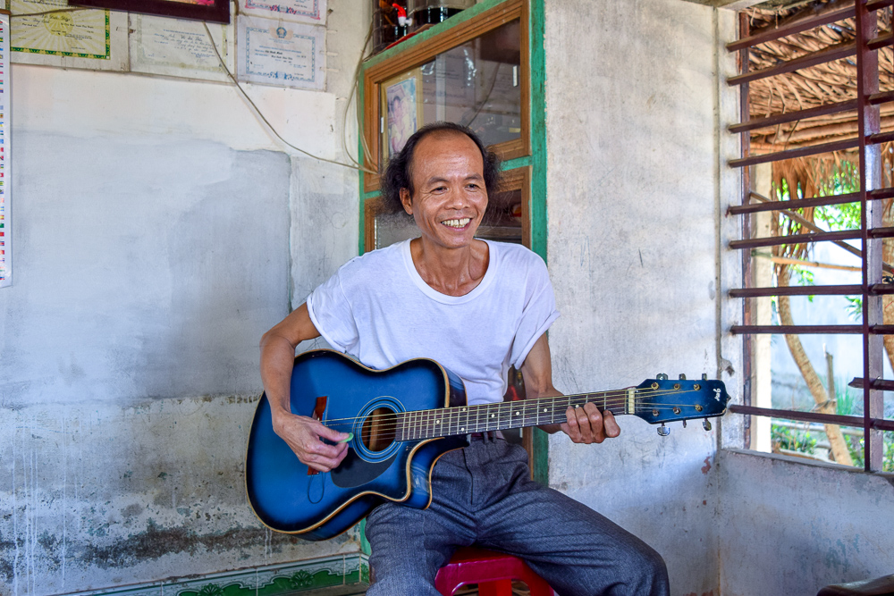 This picture of vietnam shows a local man holding a guitar. He is a war hero with an impressive yet tragic story but you'd never know from that smile