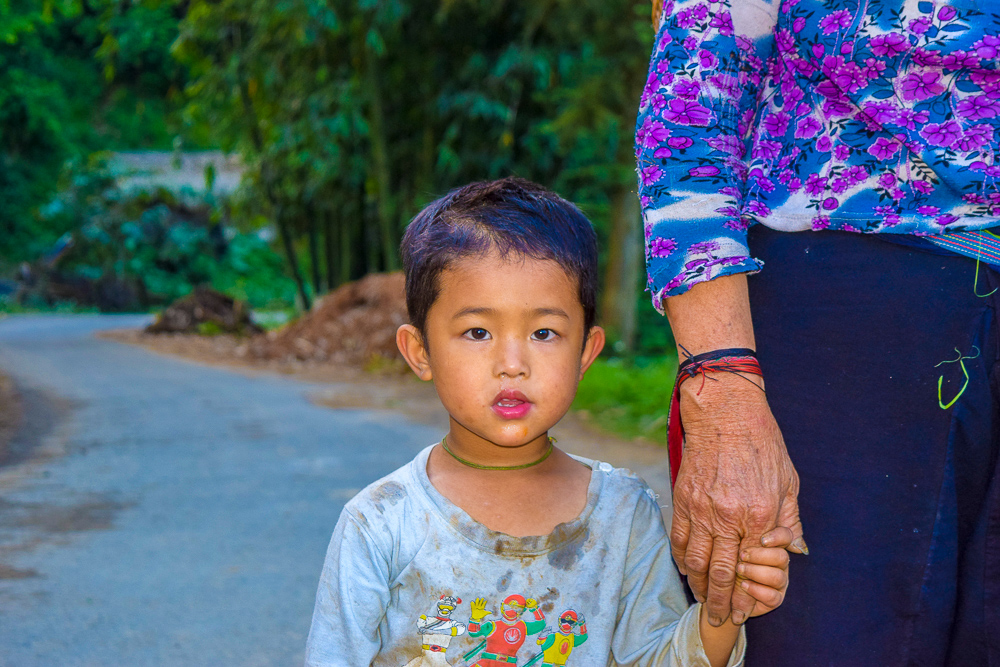 A sweet looking Vietnamese boy holding the frail hand of his mother