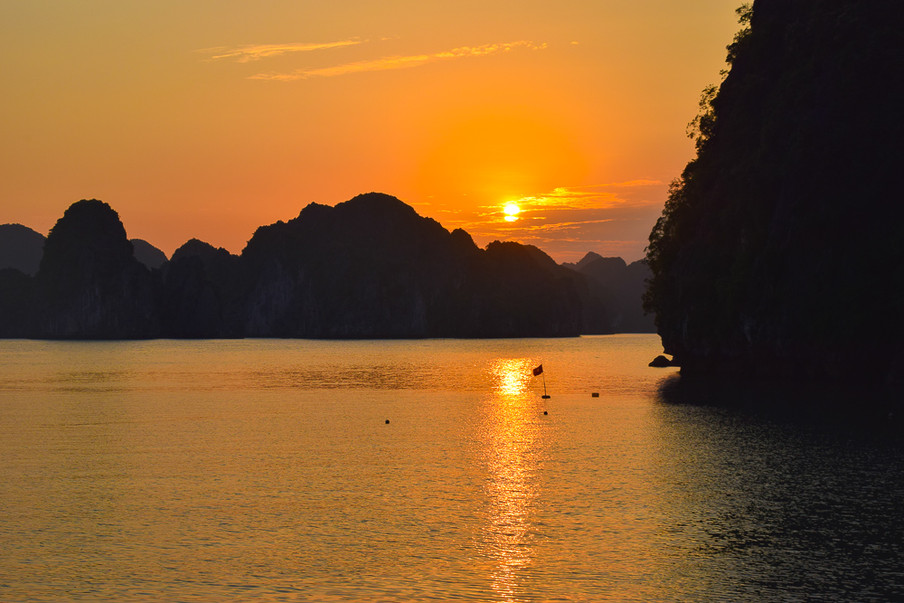 Possible my favourite picture of Vietnam - a beautiful sunset photo taken in Halong Bay. The Sky is lit up an impressive orange that reflects in the water below